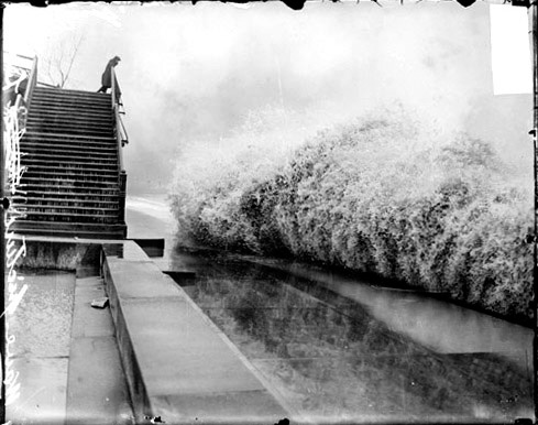 A wave breaking on the shore of Lake Michigan in Chicago while a man watches from a bridge.