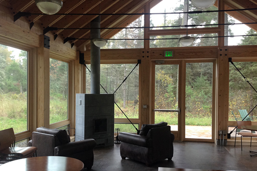 The new Trail Center is both cozy, with leather chairs and a wood stove, and has floor to ceiling views of the surrounding pines.